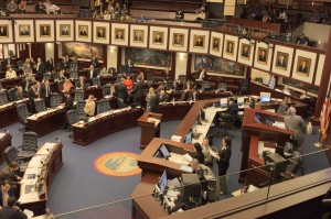 Yay Or Nay: Legislators in The Florida House of Representatives look to a video screen on the far end of the room for yays and nays on a piece of legislation during an April 9 session.Each chamber looks just like you'd expect - a large, bustling room where minds do battle over the future of Florida law. In the House, a big video screen tallies representatives' yays and nays as they vote on proposed bills while they simultaneously walk up and down the room conferring with one another. The pace is quick but not necessarily focus, with some Representatives glaring at the screen and others holding private conversations with others. TOMÁS MONZÓN\THE REPORTER