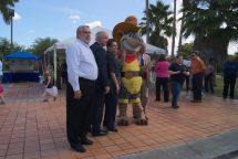 Attendees of a ribbon-cutting ceremony for the new Westchester Circulator pose with the mascot from local business, Texas Roadhouse. BY TOMAS MONZON